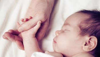 Newborn baby and his father's hand – care and safety concept