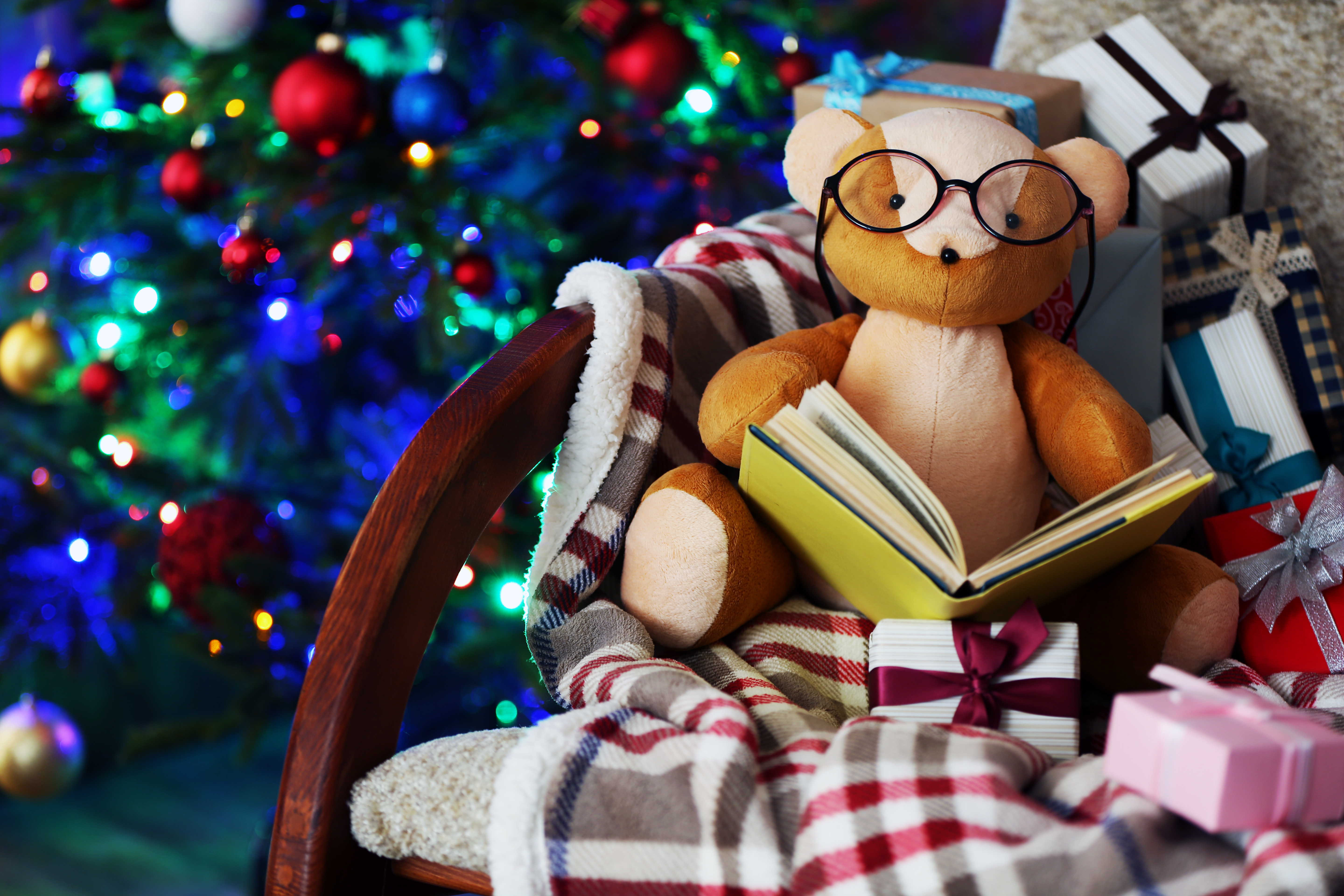 Teddy bear with book and gift boxes in rocking chair