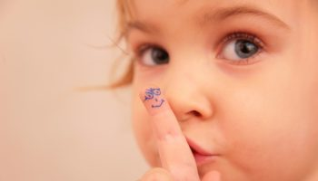 little girl and finger with painted face